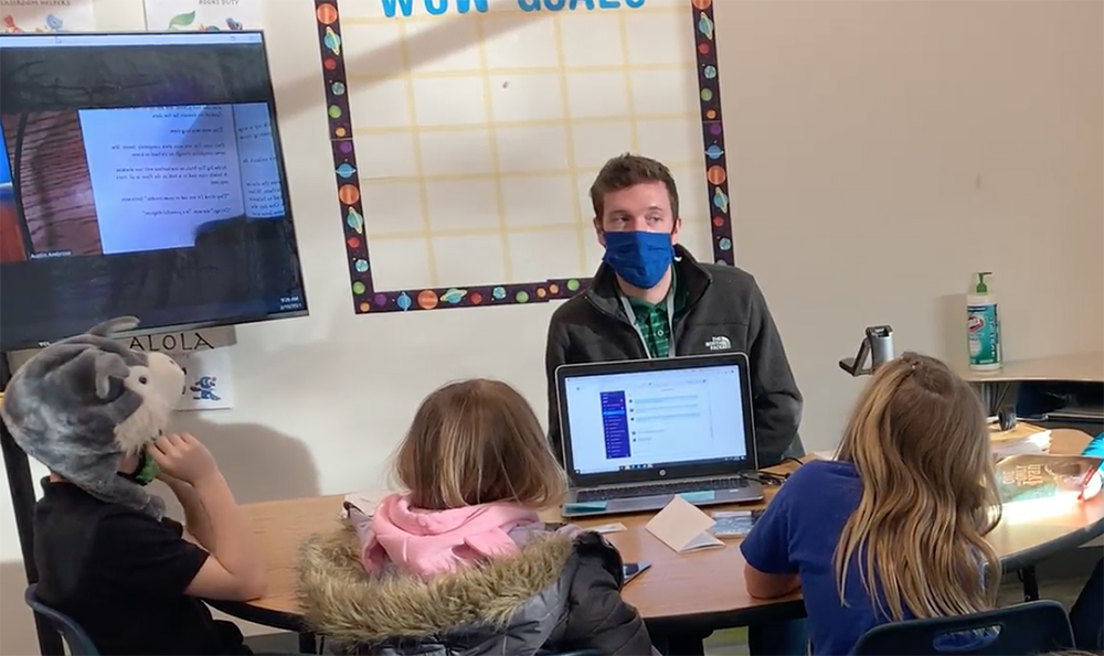 The teacher Austin Ambrose wears a mask while talking to a small group of students sitting at a table.